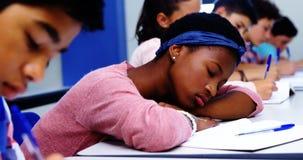 Vermoeide studentenslaap in klaslokaal stock footage