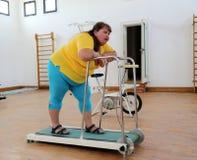 Vermoeide te zware vrouw op trainertredmolen Stock Foto's