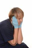Vermoeide verpleegster met in hand hoofd Stock Foto