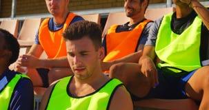 Vermoeide voetballers die in het stadion 4k zitten stock footage