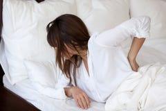 Vermoeide vrouw die aan rugpijn lijden die slechte slaap hebben royalty-vrije stock foto