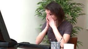 Vermoeide vrouw die bij een computer werken stock videobeelden