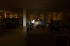 Vermoeide Vrouw die Computer in Donker Bureau met behulp van royalty-vrije stock foto's