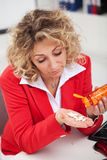 Vermoeide vrouw die pillen in bureau neemt Stock Afbeeldingen