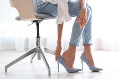 Vermoeide vrouw die schoenen opstijgen op kantoor royalty-vrije stock afbeelding