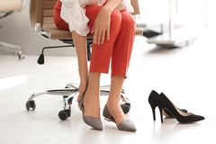Vermoeide vrouw die schoenen opstijgen op kantoor royalty-vrije stock foto's
