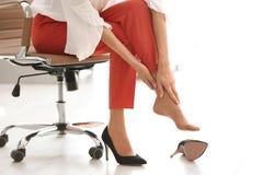 Vermoeide vrouw die schoenen opstijgen op kantoor stock fotografie