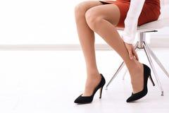 Vermoeide vrouw in hoog gehielde schoenen op kantoor royalty-vrije stock afbeeldingen