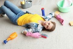 Vermoeide vrouw met het schoonmaken van levering die op tapijt liggen stock fotografie