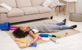 Vermoeide vrouw met het schoonmaken van levering die op vloer liggen stock fotografie