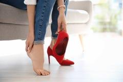 Vermoeide vrouw met mooie benen die schoenen opstijgen royalty-vrije stock fotografie