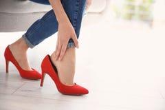 Vermoeide vrouw met mooie benen die schoenen opstijgen stock foto's