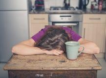 Vermoeide vrouw met thee in keuken Stock Foto's