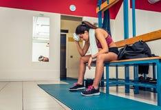 Vermoeide vrouw na een training in de gymnastiekkleedkamer Stock Afbeelding