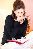 Vermoeide vrouw van lezingsboek Stock Afbeeldingen