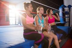 Vermoeide vrouwelijke atleten die met waterflessen zitten op boksring stock afbeeldingen
