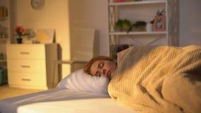 Vermoeide vrouwelijke slaap in bed, dagdutje, weekendluiheid, huisontspanning stock videobeelden