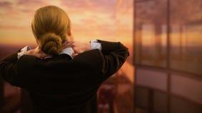 Vermoeide vrouwelijke werknemer die halsoefeningen doen, die van zonsondergang van bureauvenster genieten stock videobeelden