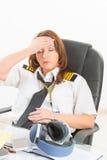 Vermoeide vrouwenluchtvaartlijn proef in het bureau stock foto