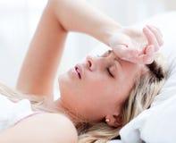 Vermoeide vrouwenslaap op een bed Stock Afbeelding
