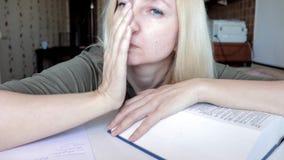 Vermoeide vrouwenzitting door de lijst en slaap, met een hoofd op een groot boek, onderwijs en studieconcept stock footage
