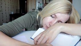 Vermoeide vrouwenzitting door de lijst en slaap, met een hoofd op een groot boek, onderwijs en studieconcept stock video