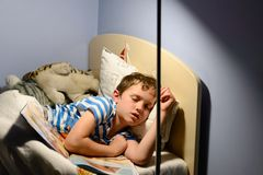 Vermoeide weinig jongenskind viel in slaap stock foto's