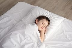 Vermoeide weinig jongensslaap in bed, gelukkige bedtijd in witte slaapkamer Stock Afbeelding