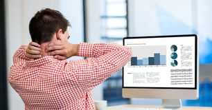 Vermoeide zakenman die grafieken in Desktoppc bekijken terwijl het werken van bureau Royalty-vrije Stock Foto's