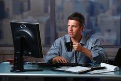 Vermoeide zakenman die laat in bureau werkt stock afbeelding