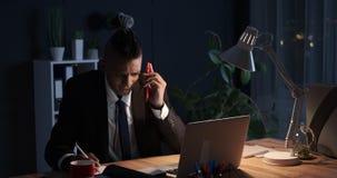 Vermoeide zakenman die nota's nemen en het bureauwerk laat in nacht beëindigen stock video