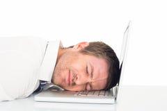 Vermoeide zakenman die op laptop rusten Stock Foto's