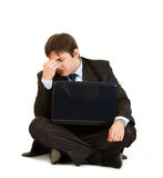 Vermoeide zakenmanzitting op vloer met laptop Royalty-vrije Stock Foto's
