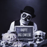 Vermomde mens met bord met tekst gelukkig Halloween, b&w stock fotografie