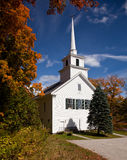 Vermont Church in Fall. Autumnal shot of the typical Vermont church in fall as the bright trees turn orange and red Royalty Free Stock Image