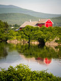 Vermont Farm by River. Red painted farm buildings on the banks of the Connecticut river in Vermont Stock Photos