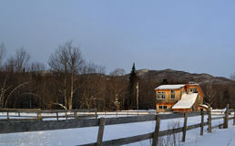 Vermont House in the Mountains. Beautiful sunlit house in the mountains with a fence in the forground on a snowy day Royalty Free Stock Photos