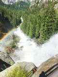 Vernal Falls Waterfall in Yosemite. Yosemite National Park, USA. View from the top of vernal falls with part of a rainbow and green trees royalty free stock photography