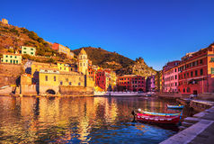 Vernazza village, church, boats and sea harbor on sunset. Cinque Royalty Free Stock Photography