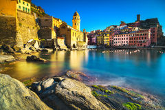 Vernazza village, church, rocks and sea harbor on sunset. Cinque Royalty Free Stock Image