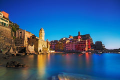 Vernazza village, church, rocks and sea harbor on sunset. Cinque Stock Image
