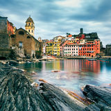 Vernazza village, church, rocks and sea harbor on sunset. Cinque Royalty Free Stock Photography
