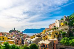 Vernazza village with typical colorful multicolored buildings houses, Castello Doria castle on rock, green hills and Genoa Gulf, L stock images