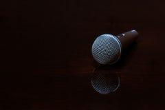 Vernehmbares Mikrofon auf dunkler polierter Oberfläche Stockfoto