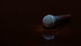 Vernehmbares Mikrofon auf dunkler polierter Oberfläche Stockfotos