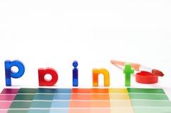 Vernici le lettere, la spazzola ed i campioni di colore di carta Immagini Stock