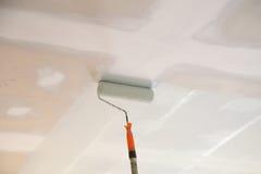 Verniciatura del soffitto del gesso del gesso con il rullo immagini stock