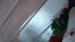 Verniciatura della spazzola di legno della parete Passi con le pitture di una spazzola una superficie di legno video d archivio
