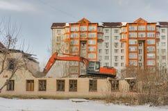 Vernieling van een huis met een oranje graver Royalty-vrije Stock Afbeelding