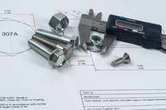 Vernier caliper and assorted screw, nuts and bolts. Assorted screw, nuts and bolts royalty free stock photos